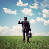Businessman standing in the field and points a finger at somethi Stock Photos