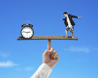 Businessman standing on finger seesaw vs clock Stock Photo