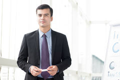 Businessman standing beside flip chart about to make a presentation stock images
