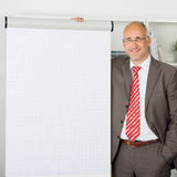 Businessman Standing By Flipchart In Office Royalty Free Stock Image