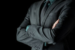 Businessman standing with folded arms in a classic black suit. Closeup view of the torso of a businessman standing with folded arms in a classic black suit with Stock Image