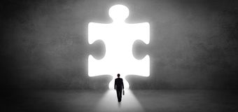 Businessman standing in front of a big puzzle piece royalty free stock photography