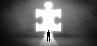 Businessman standing in front of a big puzzle piece. Businessman standing and looking to a big puzzle piece royalty free stock images