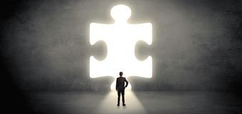 Businessman standing in front of a big puzzle piece royalty free stock photos