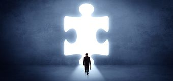 Businessman standing in front of a big puzzle piece royalty free stock image