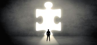 Businessman standing in front of a big puzzle piece stock photography