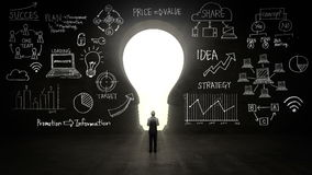 Businessman Standing in front of black, shape of bulb light, Business plan and various graph in black wall.