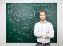 Businessman standing in front of a blackboard Stock Photo
