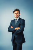 Businessman arms crossed. Businessman standing in front of blue background arms crossed Stock Photos