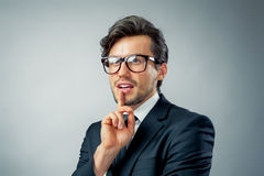 Businessman thinking. Businessman standing in front of blue background thinking with finger on chin Stock Photo