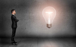Businessman standing in front of bright light bulb Stock Images