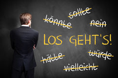 Businessman standing in front of a chalkboard with stroked words like could and should and `Let`s go` in the middle Royalty Free Stock Image