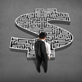 Businessman standing in front of 3d money shape maze. On concrete ground Royalty Free Stock Image