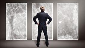 Businessman standing in front of 3 doors stock photo