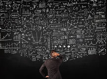 Businessman standing in front of drawn charts on a blackboard. Young businessman standing in front of sketched charts and signs on a blackboard Royalty Free Stock Image