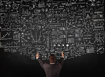 Businessman standing in front of drawn charts on a blackboard Stock Photography