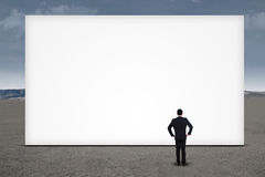 Businessman standing in front of empty board Royalty Free Stock Photos