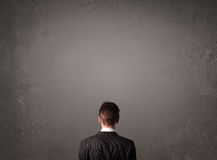 Businessman standing in front of an empty wall. Young businessman standing in front of a wall with copy space Royalty Free Stock Images