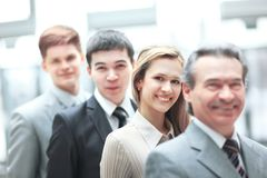 Businessman standing in front of his business team on blurred office background stock photo