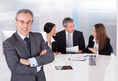 Businessman standing in front of his colleagues Stock Photos
