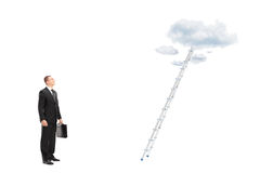 Businessman standing in front of a ladder with clouds looking up Royalty Free Stock Image