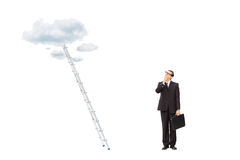 Businessman standing in front of a ladder Royalty Free Stock Images