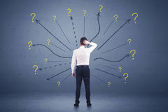 Businessman standing in front lines and question mark signs conc Stock Photo