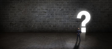 Businessman standing in front of a portal shaped as a questionmark Stock Image
