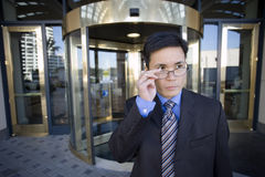 Businessman standing in front of revolving door, adjusting spectacles Royalty Free Stock Image
