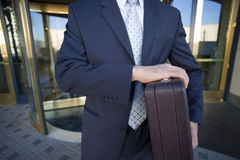 Businessman standing in front of revolving door, carrying briefcase, front view, mid-section Stock Photo