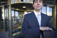 Businessman standing in front of revolving door, carrying briefcase, smiling, front view, portrait Stock Photos