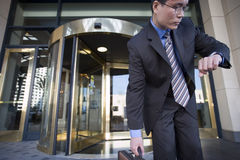 Businessman standing in front of revolving door, checking time on wristwatch, picking up briefcase Royalty Free Stock Photography