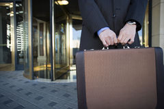 Businessman standing in front of revolving door, holding briefcase, mid-section Royalty Free Stock Photos