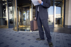 Businessman standing in front of revolving door, holding document and briefcase, low section Royalty Free Stock Photos