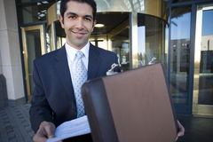 Businessman standing in front of revolving door, taking document from briefcase, smiling, portrait Royalty Free Stock Photo