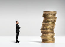Businessman standing in front of a stack scale rouble coins Royalty Free Stock Photography