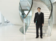 Businessman Standing In Front Of Stairs. Full length portrait of a confident businessman with folder standing in front of stairs Royalty Free Stock Photos
