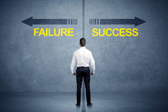 Businessman standing in front of success and failure arrow conce Stock Photography