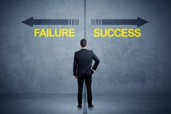 Businessman standing in front of success and failure arrow conce. Pt on grungy background Royalty Free Stock Photography
