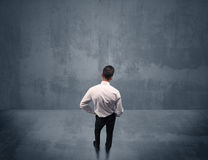 Businessman standing in front of urban wall Stock Images