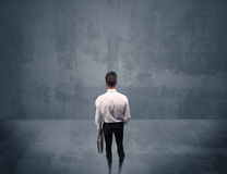 Businessman standing in front of urban wall Royalty Free Stock Images