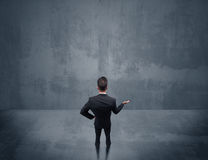 Businessman standing in front of urban wall Stock Photos