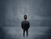 Businessman standing in front of urban wall Royalty Free Stock Image