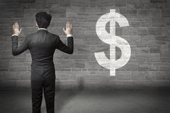 Businessman standing in front of a wall dollar Stock Images