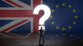 Businessman standing in front of a wall with the union jack and the eu flag with question-mark portal. Businessman standing in front of a wall with the union stock photo