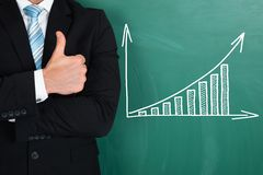 Businessman standing by graph drawn on chalkboard Royalty Free Stock Image