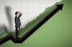 Businessman standing on a graph and looking up on the results. Successful businessman standing on a graph and looking up on the results Royalty Free Stock Image