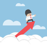 Businessman standing on a graph soaring through the clouds Royalty Free Stock Photography