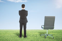 Businessman standing on a green grass and looks away Royalty Free Stock Image