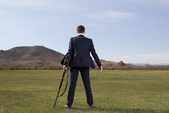 Businessman standing on green meadow with a hunting rifle Royalty Free Stock Image